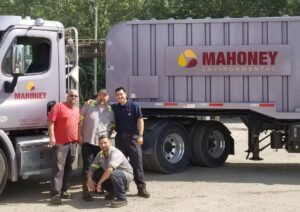 Ricardo with drivers in front of Mahoney truck Employee Spotlight